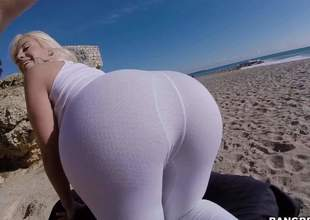 Curvy sexy Blondie Fesser in green ripped fishnet hose bends over and shows off her large bubble butt on the beach. She shakes her wazoo in the sun and finger fucks her arsehole