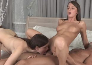 2 beauties are giving each other an agonorgasmos whilst fucked in a trio